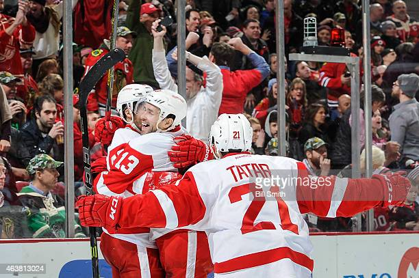 Pavel Datsyuk and Tomas Tatar celebrate with Darren Helm of the Detroit Red Wings after Helm scored against the Chicago Blackhawks in the third...