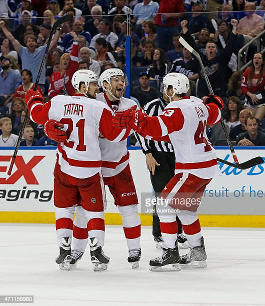 Pavel Datsyuk is congratulated by Tomas Tatar and Darren Helm of the Detroit Red Wings after scoring a goal against the Tampa Bay Lightning during...