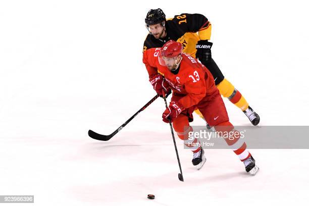 Pavel Datsyuk of Olympic Athlete from Russia and Brooks Macek of Germany compete for the puck in the third period during the Men's Gold Medal Game on...