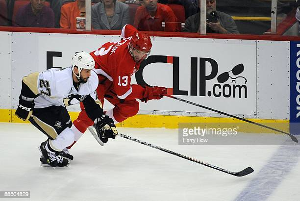 Pavel Datsyuk of the Detroit Red Wings and Craig Adams of the Pittsburgh Penguins skate up ice along the left wing boards during Game Seven of the...