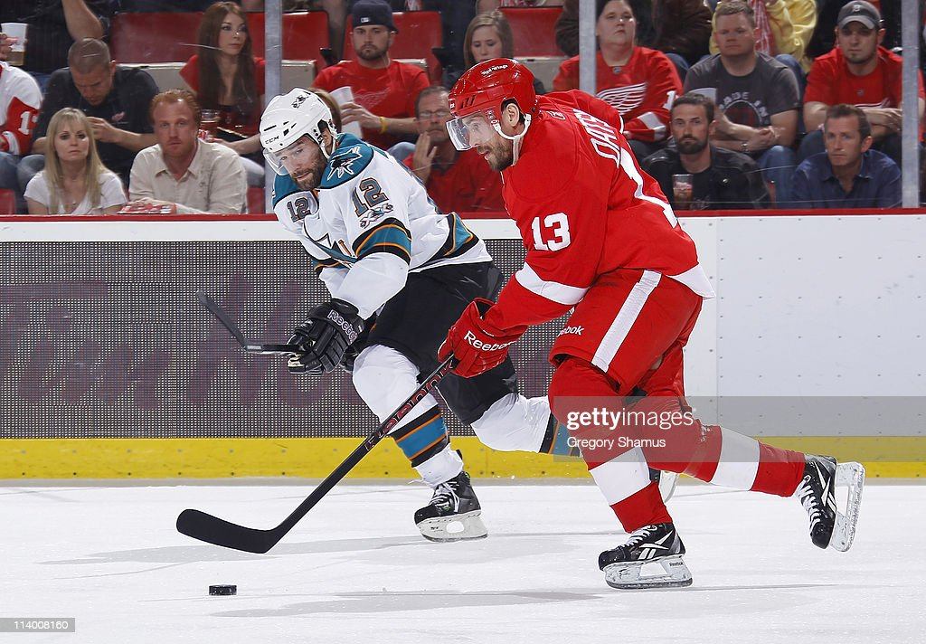 Pavel Datsyuk #13 of the Detroit Red Wings controls the puck in front of Patrick Marleau #12 of the San Jose Sharks during the first period in Game Six of the Western Conference Semifinals during the 2011 NHL Stanley Cup Playoffs on May 10, 2011 at Joe Louis Arena in Detroit, Michigan.