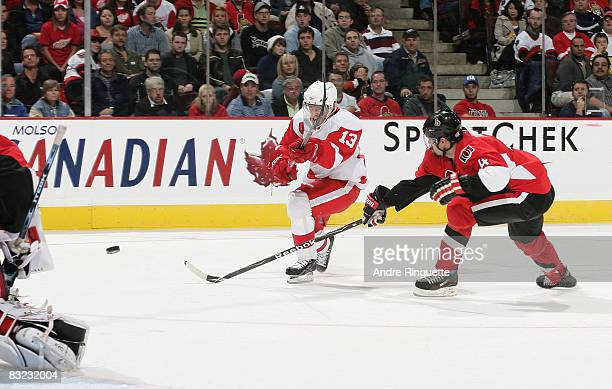 Pavel Datsyuk of the Detroit Red Wings fires a backhand shot as Chris Phillips of the Ottawa Senators reaches for a deflection at Scotiabank Place on...