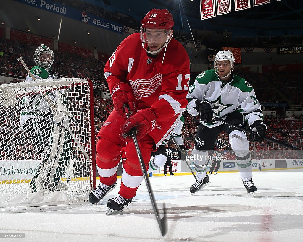 Pavel Datsyuk #13 of the Detroit Red Wings goes after the puck behind the net as Alex Goligoski #33 of the Dallas Stars gives chase during an NHL game at Joe Louis Arena on November 7, 2013 in Detroit, Michigan. Dallas defeated Detroit 4-3 in OT