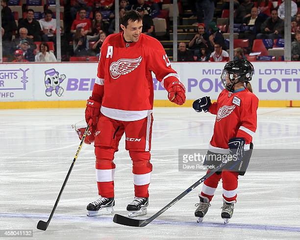 Pavel Datsyuk of the Detroit Red Wings greets the youth player of the game on Hockey Fights Cancer night Abby Pieper before a NHL game against the...