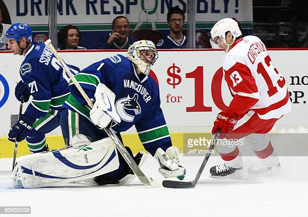 Pavel Datsyuk of the Detroit Red Wings looks for a rebound as Roberto Luongo of the Vancouver Canucks makes a save during their game at General...