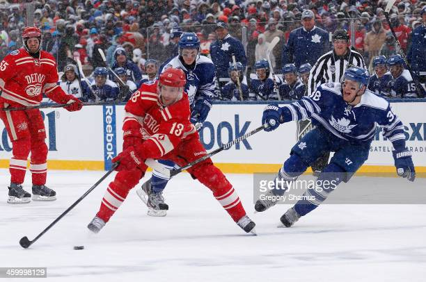 Pavel Datsyuk of the Detroit Red Wings looks to avoid Frazer McLaren of the Toronto Maple Leafs in the second period during the 2014 Bridgestone NHL...