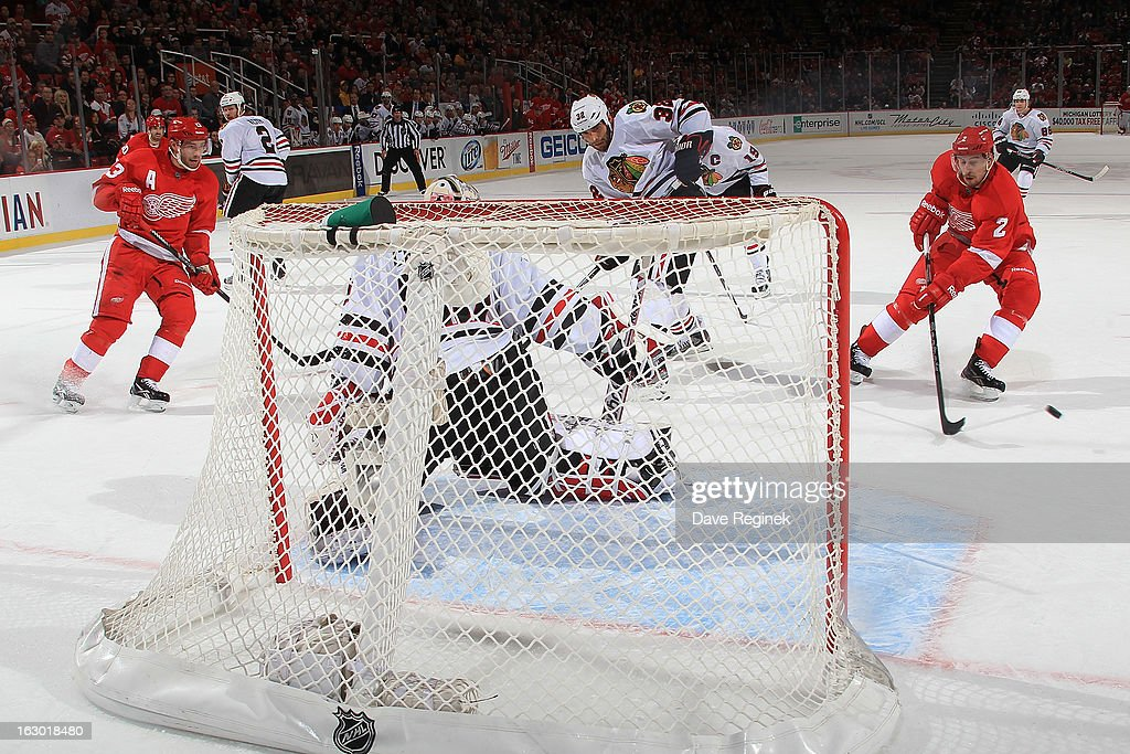 Pavel Datsyuk #13 of the Detroit Red Wings passes the puck to teammate Brendan Smith #2 for a scoring attempt on Corey Crawford #50 of the Chicago Blackhawks during an NHL game at Joe Louis Arena on March 3, 2013 in Detroit, Michigan. Chicago won 2-1 in a shoot-out