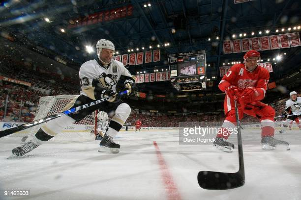 Pavel Datsyuk of the Detroit Red Wings races to the corner for the puck with Bill Guerin of the Pittsburgh Penguins during a NHL preseason game at...