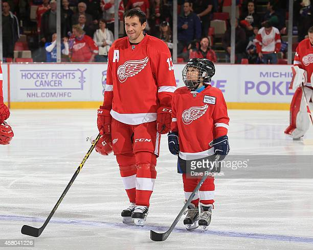 Pavel Datsyuk of the Detroit Red Wings stands next to the youth player of the game on Hockey Fights Cancer night Abby Pieper before a NHL game...