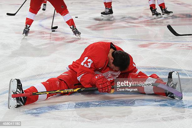 Pavel Datsyuk of the Detroit Red Wings stretches on the ice with lavender tape on his stick for Hockey Fights Cancer night prior to a NHL game...
