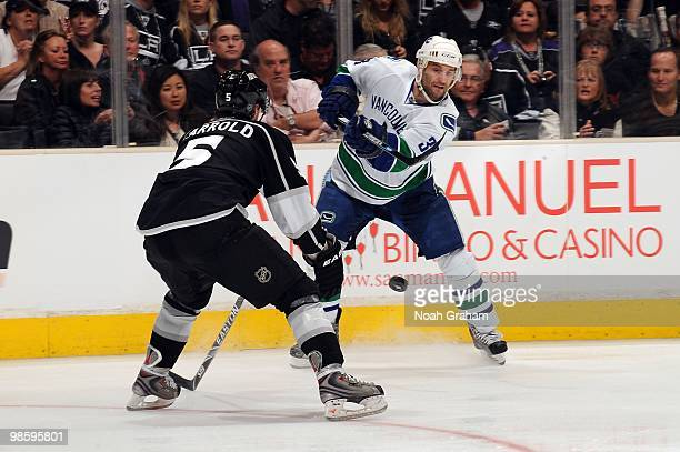 Pavel Demitra of the Vancouver Canucks passes the puck against Peter Harrold of the Los Angeles Kings in Game Three of the Western Conference...