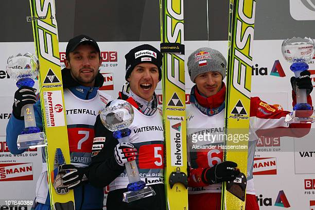 Pavel Karelin of Russia Simon Ammann of Switzerland and Adam Malysz of Poland celebrate at the podium after the training round for the FIS Ski...