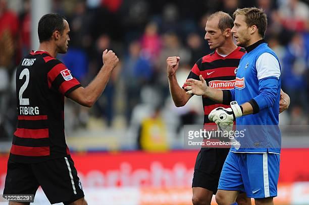Pavel Krmas of Freiburg celebrates with team mates Oliver Barth and goalkeeper Oliver Baumann after winning the Bundesliga match between SC Freiburg...