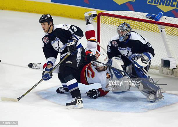 Pavel Kubina and Nikolai Khabibulin of the Tampa Bay Lightning keep their eyes on the play as Martin Gelinas of the Calgary Flames falls to the ice...