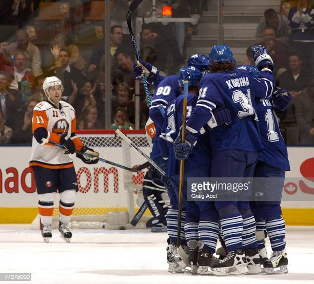 Pavel Kubina of the Toronto Maple Leafs celebrates with teammates as Andy Hilbert of the New York Islanders looks on at the Air Canada Centre October...