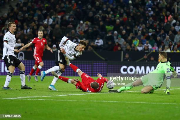 Pavel Nekhajchik of Belarus is tackled by Robin Koch of Germany inside the area which later leads to a penalty awarded to Belarus during the UEFA...