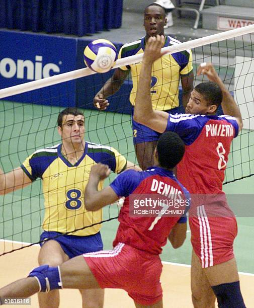 Pavel Pimienta and Angel Dennis jump in an effort to reach a ball as Douglas Chiarotti of Brazil looks on in their volleyball game against Brazil 24...