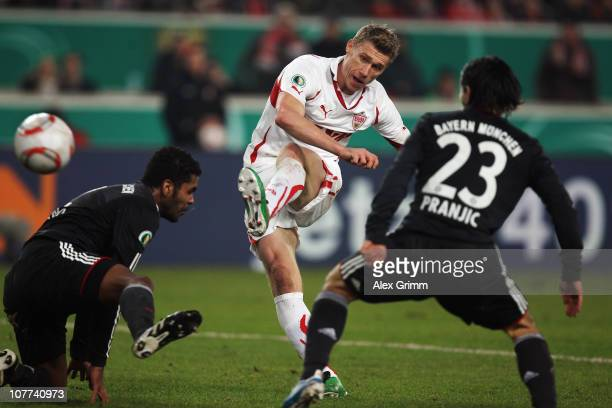 Pavel Pogrebnyak of Stuttgart scores his team's second goal against Breno and Danijel Pranjic of Muenchen during the DFB Cup round of sixteen match...
