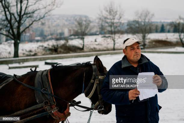 Pavel Slavchev shows his license for a horse cart in the predominantly-Roma suburb of Fakulteta on the outskirts of Sofia on December 20, 2017....