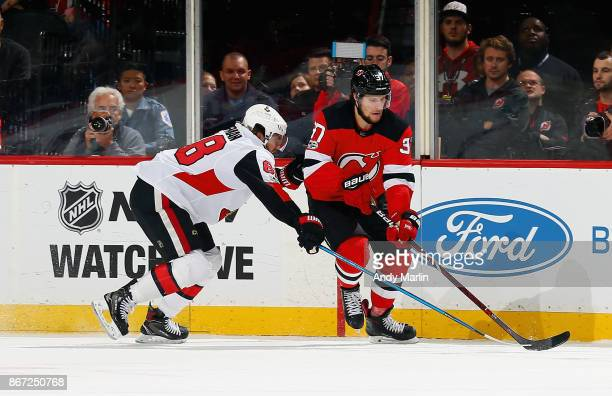 Pavel Zacha of the New Jersey Devils controls the puck while being defended by Mike Hoffman of the Ottawa Senators during the game at Prudential...