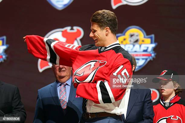 Pavel Zacha puts on his jersey after being selected sixth overall by the New Jersey Devils in the first round of the 2015 NHL Draft at BB&T Center on...