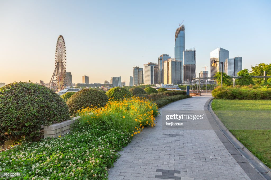 pavement  in an urban park with business district in background : Stock Photo