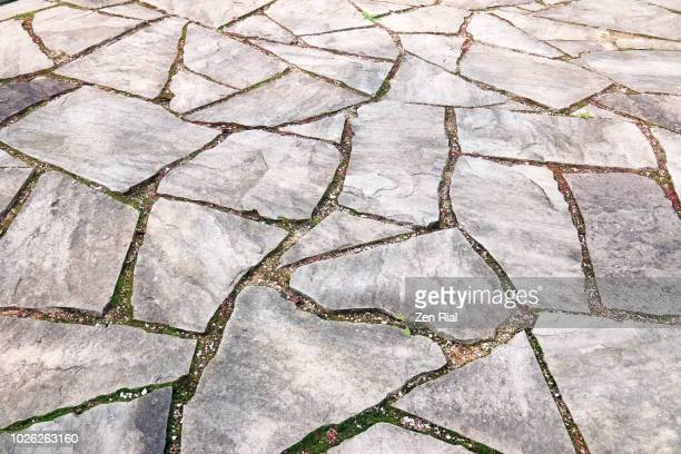 pavement reusing broken concrete pieces creating interlocking geometric shapes - paving stone stock pictures, royalty-free photos & images