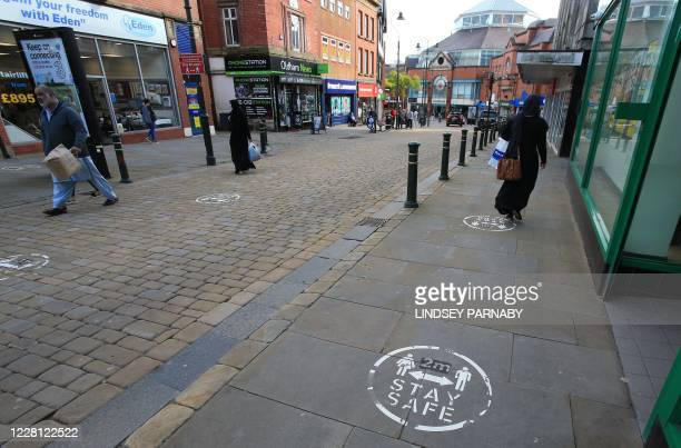 Pavement stickers ask pedestrians to social distance outside shops in Oldham Greater Manchester northwest England on August 20 2020 Oldham as of...