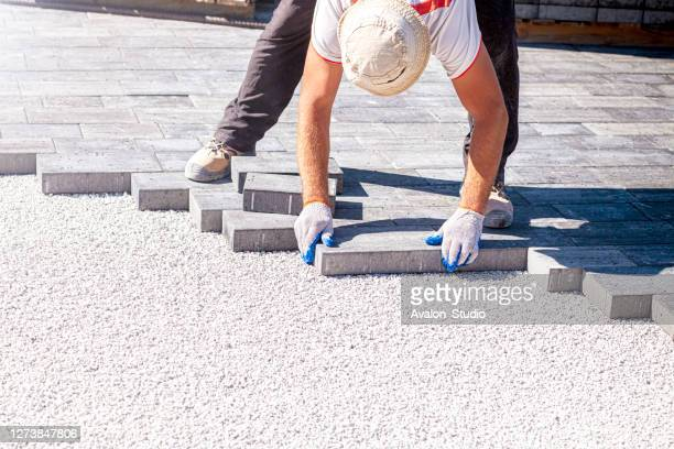 paver arranges cement paving stones - paver driveway stock pictures, royalty-free photos & images