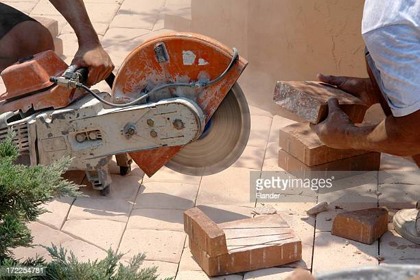 paver worker cross cuts a stone - paver driveway stock pictures, royalty-free photos & images