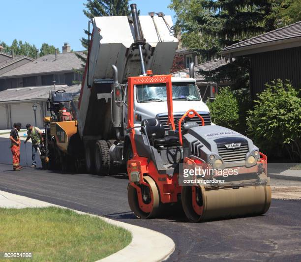 paving machine,roller and truck working on residential road - asphalt paving stock photos and pictures