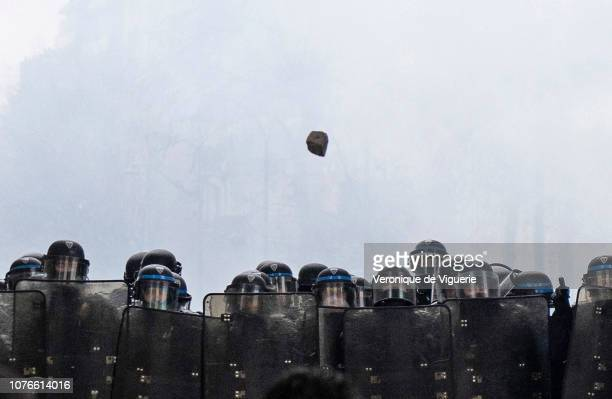 Paving stone hurtles toward riot police as they clash with protesters during a 'Yellow Vest' demonstration near the Arc de Triomphe on December 1,...