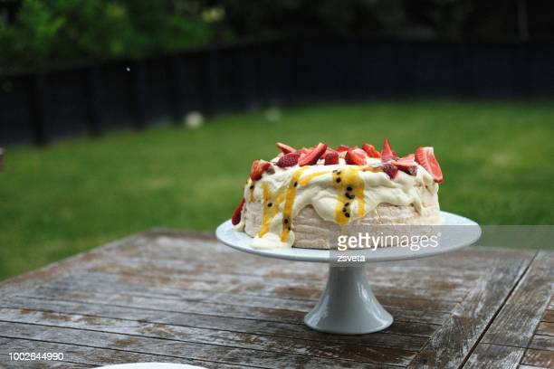Pavlova dessert om a cake stand on the outdoor wooden table