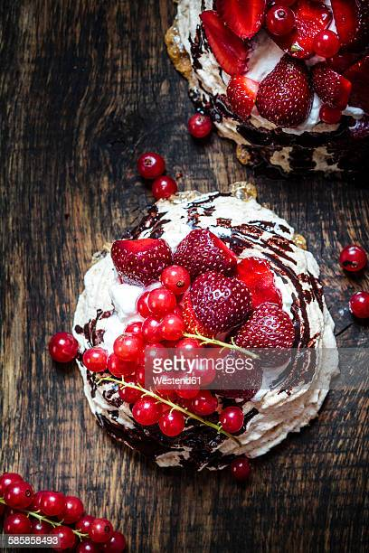 pavlova with whipped cream, fruit topping and chocolate sauce - meringue stock pictures, royalty-free photos & images