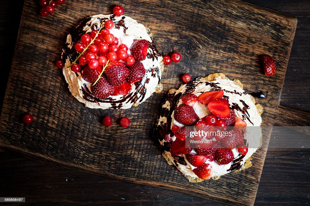 Pavlova with whipped cream, fruit topping and chocolate sauce : Stock Photo