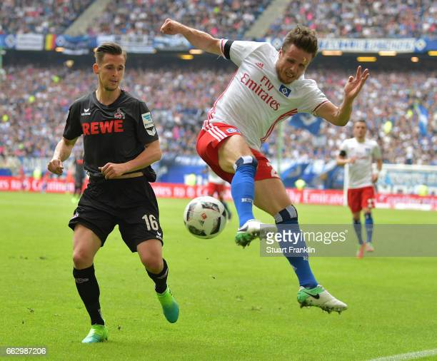 Pawel Olkowski of Cologne is challenged by Nicolai Mller of Hamburg during the Bundesliga match between Hamburger SV and 1 FC Koeln at...