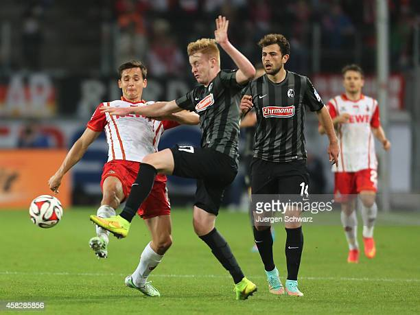 Pawel Olkowski of Cologne tackles Sebastian Kerk of Freiburg during the Bundesliga match between 1. FC Koeln and SC Freiburg at RheinEnergieStadion...
