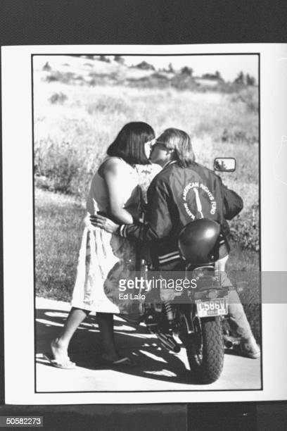 Pawnee Indian atty Walter EchoHawk kissing wife Paula goodbye before going off to work on motorcycle