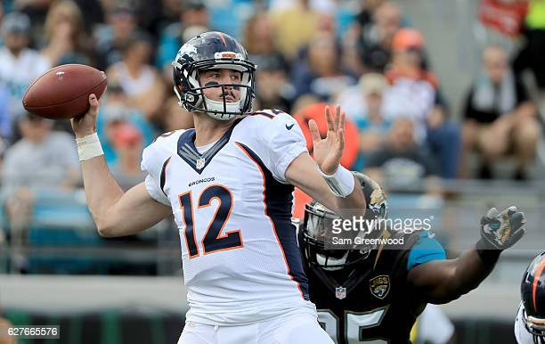 Paxton Lynch of the Denver Broncos attempts a pass as Abry Jones of the Jacksonville Jaguars closes in at EverBank Field on December 4 2016 in...
