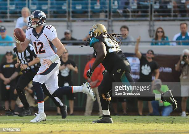 Paxton Lynch of the Denver Broncos runs for yardage as Sen'Derrick Marks of the Jacksonville Jaguars pursues at EverBank Field on December 4 2016 in...