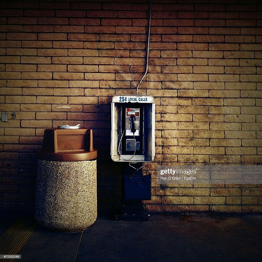 Pay Phone By Garbage Bin By Brick Wall : Stock Photo