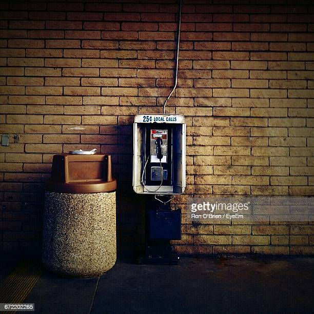 Pay Phone By Garbage Bin By Brick Wall