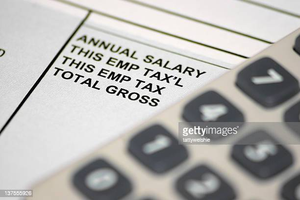 A pay slip underneath an out of focus calculator