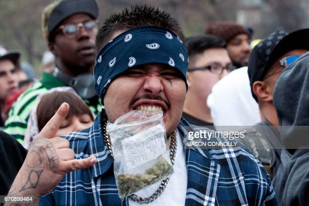 Payaso of Lamar Colorado holds a bag of marijuana with his teeth during the Denver 420 Rally at Civic Center Park in Denver Colorado on April 20 2017...