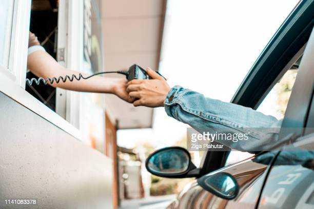 paying at drive through window - drive through stock pictures, royalty-free photos & images