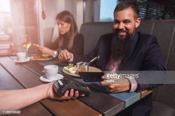 paying bills at the restaurant by smart phone - money transfer stock pictures, royalty-free photos & images