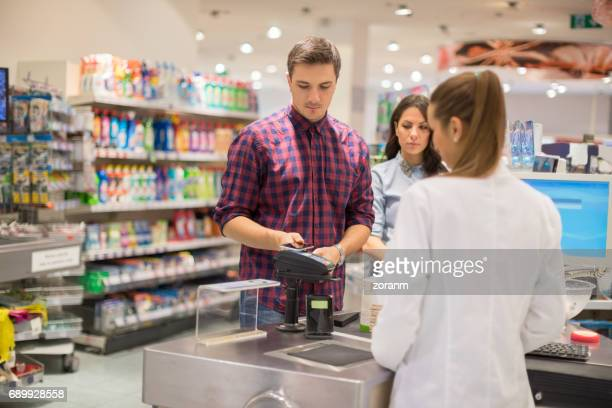 paying contactless in supermarket - convenience stock photos and pictures