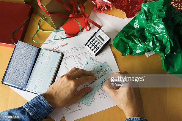 Paying for Christmas—Hands Writing Check with Calculator and Wrapping