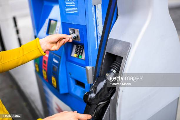 paying for fuel using a credit card at a gas station - distributore di benzina foto e immagini stock
