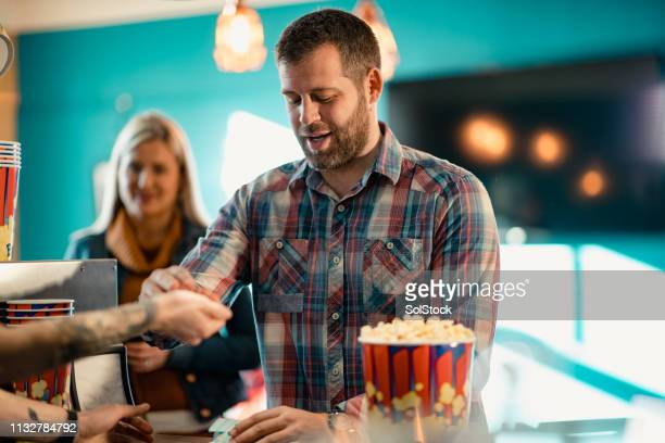paying for popcorn - film screening stock pictures, royalty-free photos & images